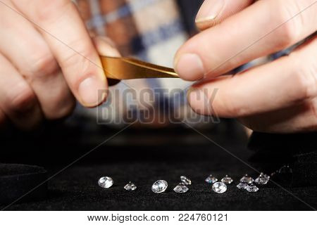 Old style diamond smuggler checking gems on velvet pad