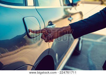 Black man's arm near car's gas tank.