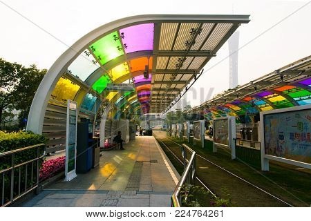 GUANGZHOU, CHINA - JANUARY 3, 2018: Guangzhou city tram station with grass covered rail track  and Canton tower in the background