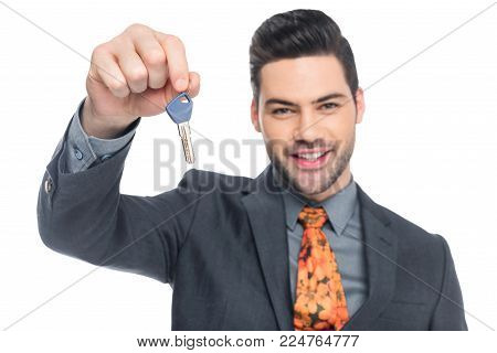 cheerful realtor holding house key, isolated on white poster