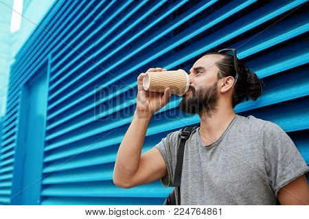 people, drinks and lifestyle concept - man drinking coffee from disposable paper cup on street over ribbed blue wall background
