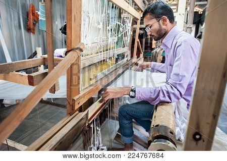 AURANGABAD, INDIA - 31 Dec 2016: People making colorful silk yarn fabric by Indian weaving loom, using the old Himroo and Paithani Weaving Technique. Silk Center at Aurangabad district, Maharashtra.