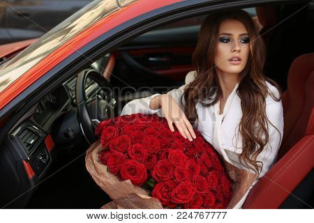 Beautiful Girl  In Elegant Dress Posing In Luxurious Car With Bouquet Of Red Roses