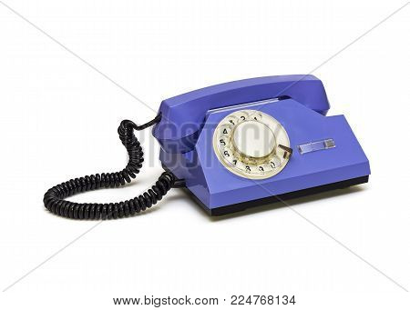 On a white background is a retro telephone with a round dialer