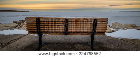 A park bench overlooking the frozen waters of Green Bay, WI.