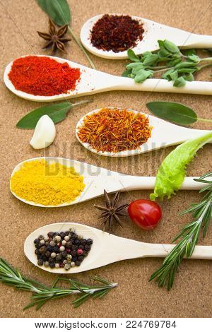 Cooking hot spicy meal. A set of four different spices in wooden spoons, fresh cherry tomatoe, garlic, rosemary and salvia, corkwood background, top view