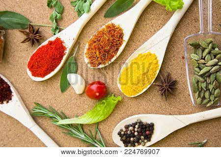 Cooking hot spicy meal. A set of four different spices in wooden spoons, dry beans, fresh cherry tomatoe, garlic, rosemary and salvia, corkwood background, top view