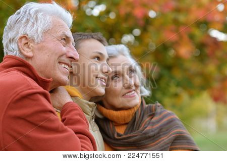 Portrait of smiling  grandparents and grandson in park