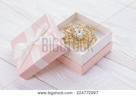 Gold brooch in the gift box on white wooden background
