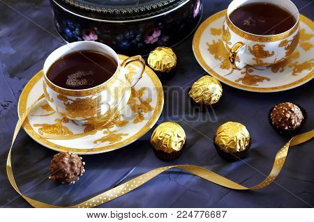 Tea ceremony, tea party. Two tea cups of gold color with black tea, candy, chocolate and box with cookies on a violet background.