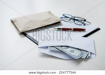 Bribery and corruption concept, bribe in the form of dollar bills, money in the envelope while making deal to agreement a real estate contract and financial corporate.