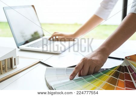 interior design or graphic designer working on project of architecture drawing with work tools and color swatches, colour chart in digital tablet at workplace.
