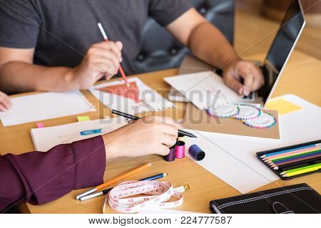 Two young professional Fashion designer colleagues working and project of drawing sketches for clothes in workplace with laptop, digital tablet and color charts, Fashion Designer Stylish Concept.
