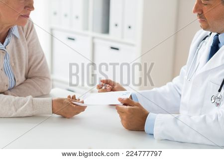 medicine, age, healthcare and people concept - close up of senior woman and doctor with prescription or referral at hospital