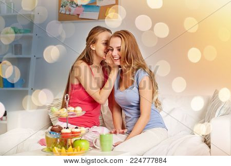 friendship, people, pajama party and communication concept - happy friends or teenage girls drinking tea with sweets and gossiping at home