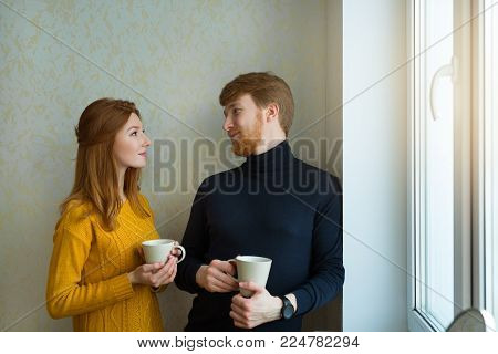 beautiful young couple man and woman standing by the window and drinking drinks in cups