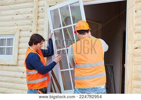 Two window fitters installing new glaziery on woodhouse