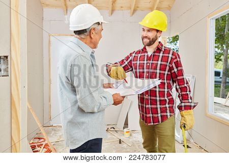 Craftsmen renovating and planning new building at construction site