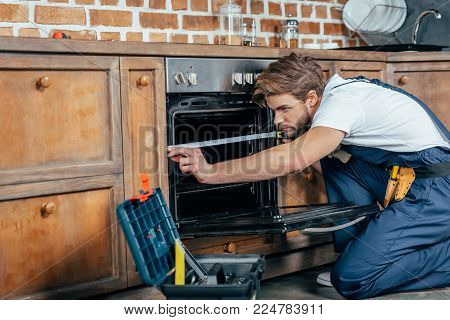 young repairman in protective workwear measuring oven with tape