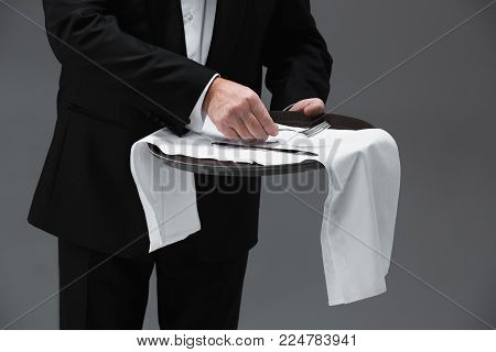 Senior waiter holding tray and standing isolated on gray studio background. concept of good service