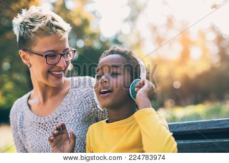 Smiling mother and little daughter having fun, listening to music on headphones. Mixed race family.