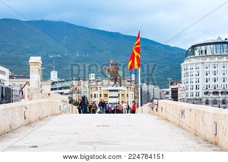 Skopje, Macedonia - September, 30, 2015: Alexander the Great statue, Macedonian flag and bridge in downtown of Skopje, people walking around