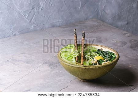Ceramic bowl with vegetarian green pea noodles with sliced cucumber, celery, spinach, quail egg yolk, pine nuts served with wooden chopsticks. Gray kitchen table. Copy space. Healthy eating.