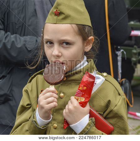 PYATIGORSK, RUSSIA - MAY 09, 2017: Girl in a forage-cap eating ice cream on the holiday of May 9, the day of victory in Russia