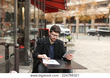 Statistician working with diagram document papers at cafe table outside in  . Hardworking man wears  dark blue shirt. Concept of using modern gadgets and Internet connection for job.