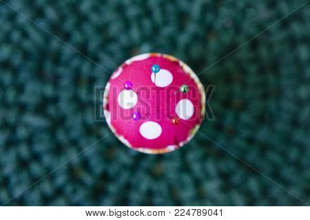 close up of a pincushion filled with colorful pins isolated on a green background