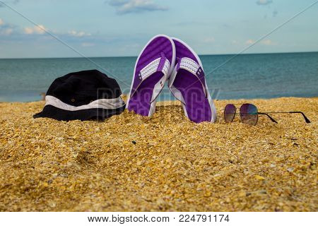 Pair of flip flops, hat and sunglasses on a sandy sea beach. Summer vacation concept