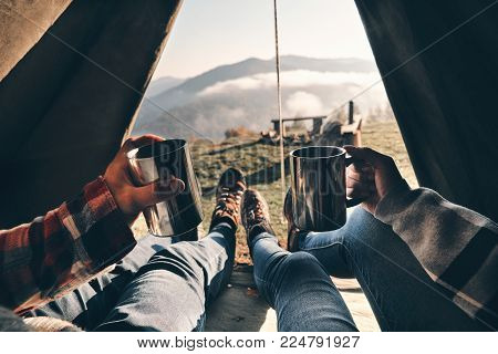 Fresh coffee to continue the adventure. Close up of young couple holding mugs while enjoying the view of mountain range from their tent