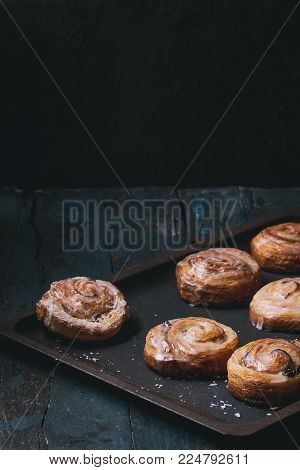 Homemade glazed puff pastry cinnamon rolls with custard and raisins on oven tray over old dark blue wooden background. Rustic style