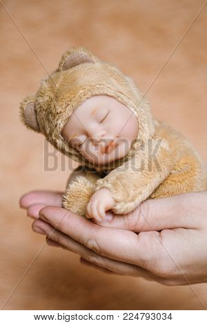 Children's doll pupsik in hands. Baby doll in sleeping condition