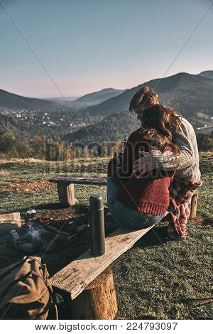 Pure feelings. Beautiful young couple having morning coffee while spending carefree time in mountains