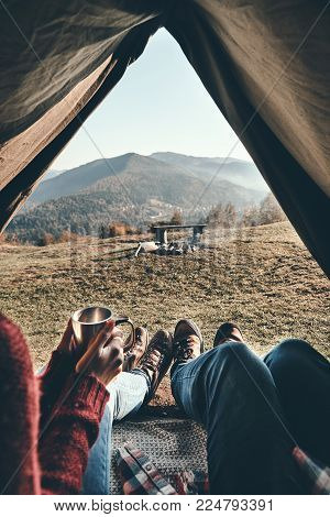 Best journey ever. Close up of young couple having morning coffee while enjoying the view of mountain range from their tent