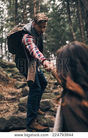 Always ready to help. Modern young couple holding hands and moving up while hiking together in the woods