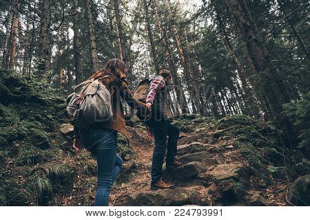 No time to relax. Rear view of modern young couple holding hands and moving up while hiking together in the woods