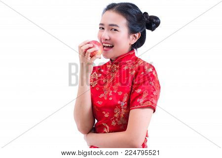 Portrait of Beautiful Young asian woman wear chinese dress traditional cheongsam or qipao. Eating red apple, isolated on white background, healthy, Chinese New Year Festivities, New Year Celebration.