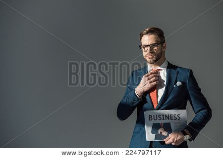 handsome young man in eyeglasses holding newspaper and adjusting necktie isolated on grey