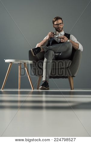 low angle view of stylish businessman with cup of coffee sitting in armchair