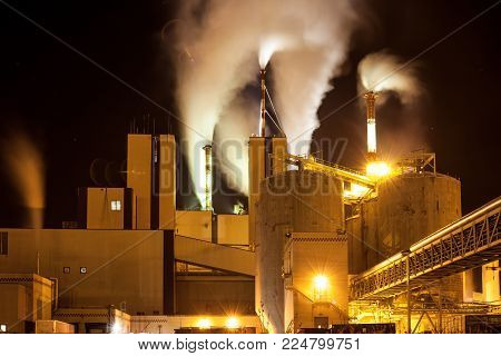 Paper mill factory with heavy smoke from production coming out of the chimneys