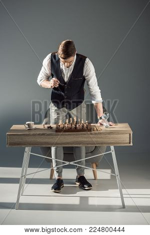 stylish young man holding eyeglasses and looking at chess board with figures