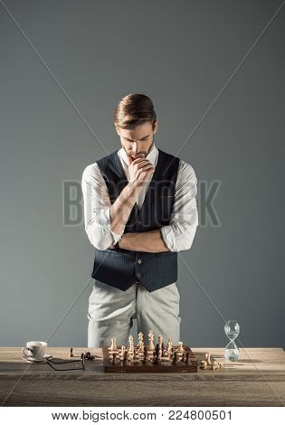 thoughtful young man looking at chess board with figures and sand clock