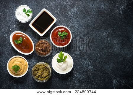 Set of sauces - ketchup, mayonnaise, mustard soy sauce, bbq sauce, pesto, mustard grains and pomegranate sauce on dark stone or metal background. Top view copy space.