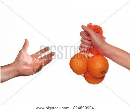 Giving orange fruit bag to a hand.
