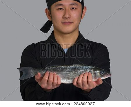 Asian cook hold a fish for sushi food portrait.
