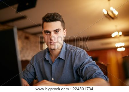 Authentic portrait of handsome young confident businessman looking at camera with laptop in office. Hipsteran and knitted sweater sitting in cafe and doing his startup ICO project. Smart casual wear. Business concept.