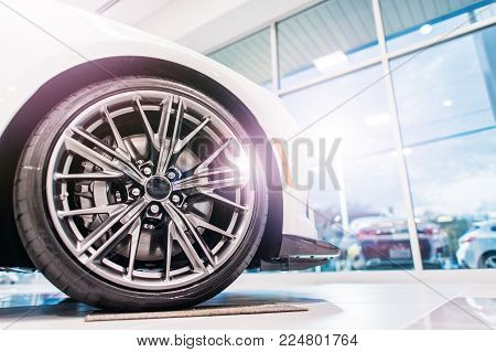 New Car For Sale in Dealership Showroom. Sporty Alloy Wheel Closeup. Automotive Industry Theme.