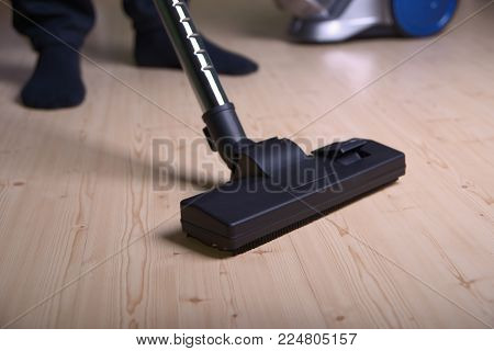 Man vacuums the floor, focus on the foreground